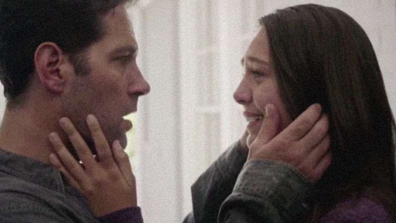Paul Rudd e Emma Fuhrmann frente a frente, com as mãos nos rostos um do outro.
