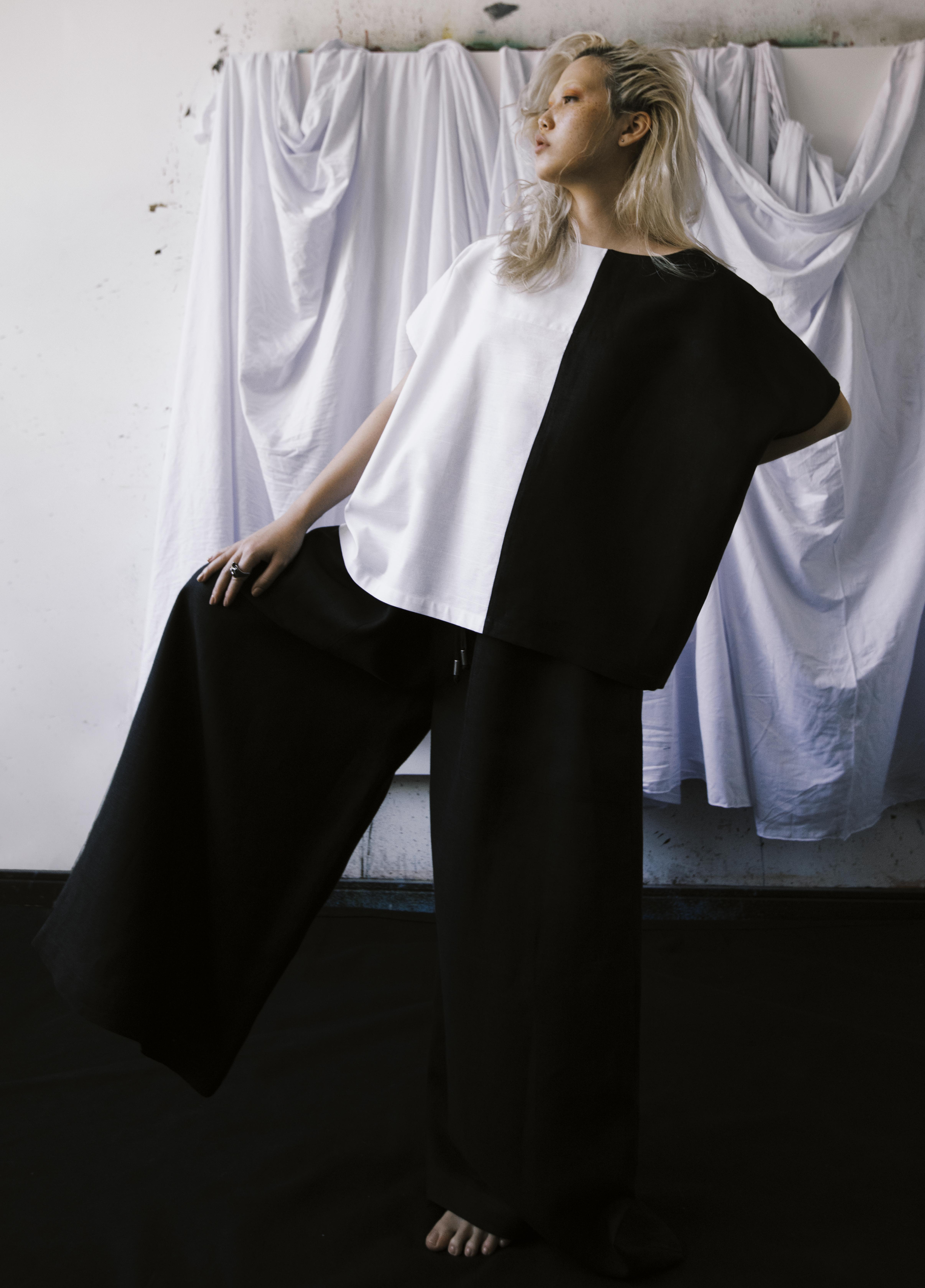 modelo vestindo camisa preta e branca e calça preta num fundo branco